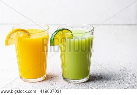 Two Glasses Of Orange, Kiwi And Avocado Smoothies, Garnished With Lemon Wedges On A White Table. Sel