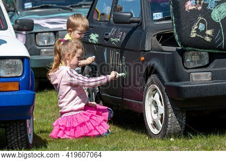 Daugmale, Latvia - May 01, 2021: Children Draw With Crayons On A Vintage Car Fiat 126