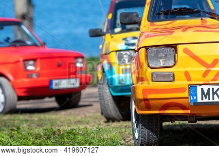 Koknese, Latvia - May 01, 2021: Several Colorful Oldtimer Pancars Rental Cars Fiat 126 Parked On The