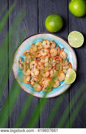 Prawns Fried With Garlic On A Blue Porcelain Plate With Whole And Sliced Limes On A Black Wooden Tab