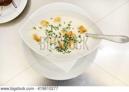Creamy Cream Soup With Croutons And Herbs In A White Plate On A Table In A Restaurant. Gastro Touris