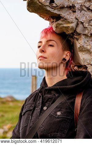 Portrait Of An Androgynous Woman Leaning Against A Stone Wall, Gazing Into Infinity With A Serene Ge