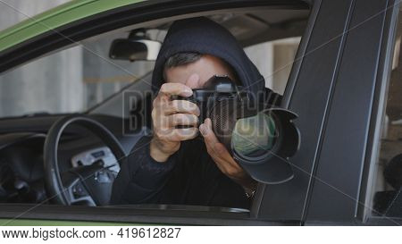 A Private Detective Or Photojournalist Secretly Takes Photos From A Car Window With A Long-focus Len