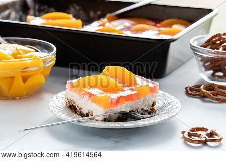 Close Up Of A Slice Of Peach Jelly Pretzel Dessert Ready For Eating With A Pan Of The Dessert In Beh