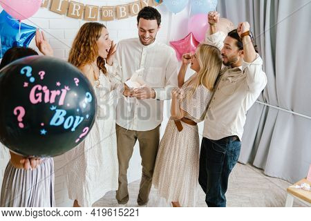 Young excited couple open surprise box during gender reveal party indoors