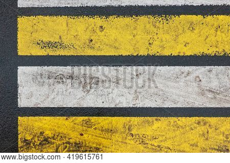 Yellow And White Pedestrian Crosswalk Lanes On Wet Asphalt. Dirty Tracks Of Cars And People Are Visi