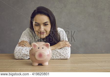 Thoughtful Woman Dreaming And Looking At Piggy Bank Sitting At Desk Studio