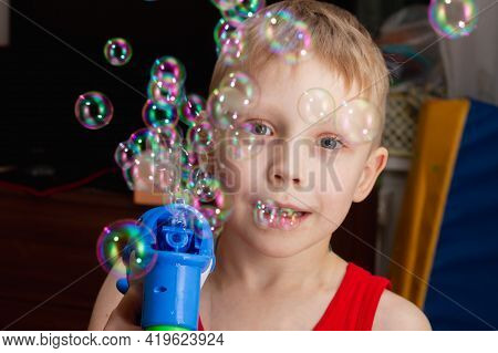 A Child Blows Soap Bubbles At Home With A Gun That Blows Soap Bubbles At Home And Smiles.
