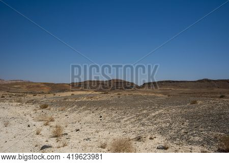 A View From The Crater In The Ramon Crater. Arid Desert View. White Sands And A Horizon Of Blue Skie