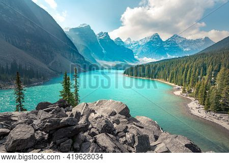 Moraine Lake In Banff National Park On A Partly Cloudy Summer Day. Mountain Range In The Back In A S