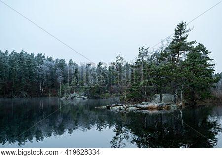 Winter Season In Scandinavia, Landscape With Lake, Rocks And Trees,  Horizontal
