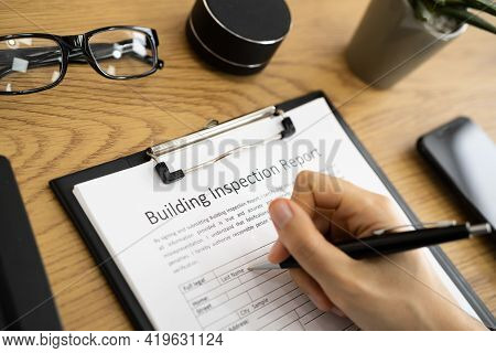 African American Inspector Checking Building Inspection Report