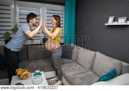 Husband And Wife High-five Twice While Standing In Their Home. A Woman In Advanced Pregnancy.