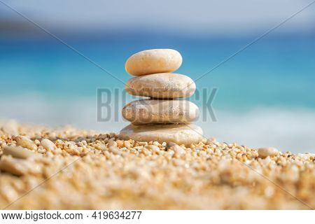 Stones Balancing On Sea Beach. Pyramid Of Pebbles On Sandy Shore. Stable Pile Or Heap In Soft Focus