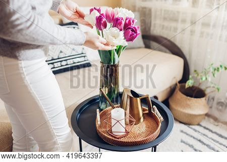 Woman Enjoys Tulips Flowers Put In Vase On Table With Tray, Watering Can And Candle. Interior And Sp