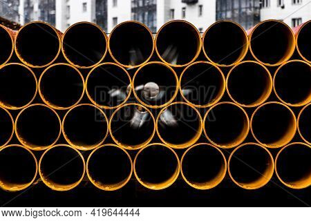 Pile Of Round Industrial Material Polyethylene Thermoplastic Pipes On A Construction Site.