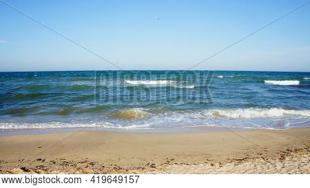 Sea. Ocean. Sea Surface, Light Waves, A Deserted Beach And A Lone Seagull In A Cloudless Sky. Horizo