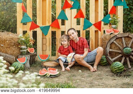 Children Having Picnic Outdoors In Summer Park. Funny Kids Eating Watermelon Outdoors In The Garden.