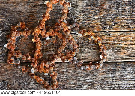 A Close Up Image Of An Old And Very Rusted Chainsaw Chain On A Wooden Table Top.