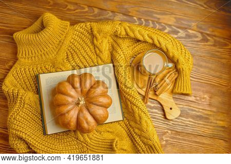 Knitted Cozy Sweater, Open Book And Pumpkin On Wooden Background. Romantic Composition. Aromatic Lat