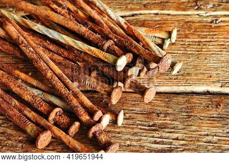 A Close Up Image Of Several Old And Very Rusted Nails On A Dark Wooden Table.