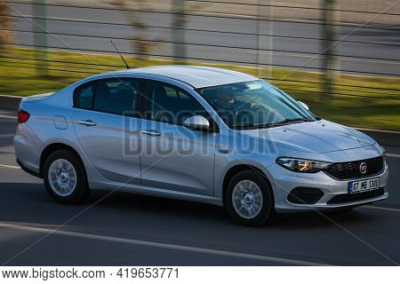 Alanya, Turkey - April 17 2021: White Fiat Albea Is Driving Fast On The Street On A Warm Summer Day