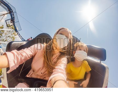 Family Wearing A Medical Mask During Covid-19 Coronavirus At An Amusement Park
