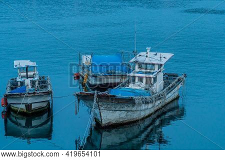 Daecheon, South Korea; April 25, 2021: Three Small Fishing Boats Anchored Off Shore In Seaport.