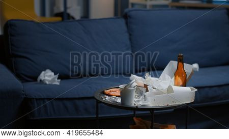 Chaos In Empty Living Room With Food Leftover And Bottle Of Beer On Table