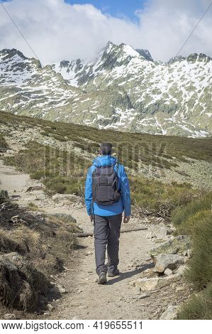Person With Backpack Walking Down The Mountain On A Sunny Day