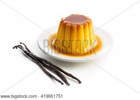 Sweet vanilla pudding and vanilla pods. Sweet dessert with caramel topping isolated on white background.