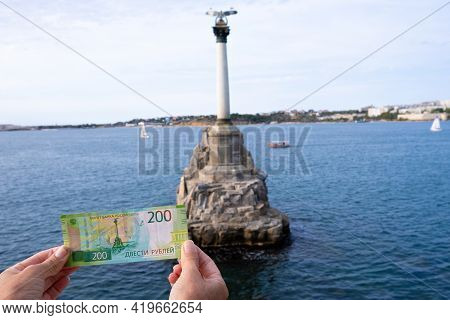 Banknote Of 200 Russian Rubles In Womens Hands Against The Background Of The Monument To Sunken Ship