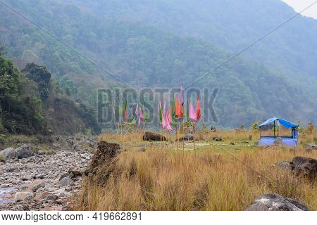 Top Of River Levees Covered In Green And Brown Vegetation , Boulders Prayer Flags . I