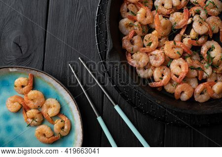 Prawns Fried With Garlic On A Blue Porcelain Plate And In A Black Cast Iron Skillet With Chopsticks