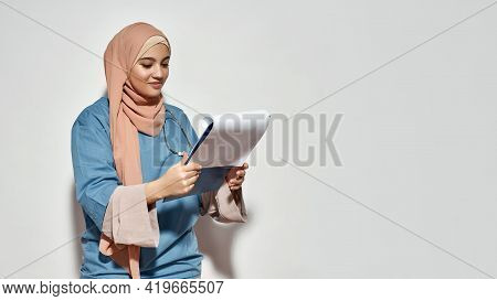 Happy Young Arabian Woman Doctor In Hijab Looking Into Notepad While Posing On Light Background With