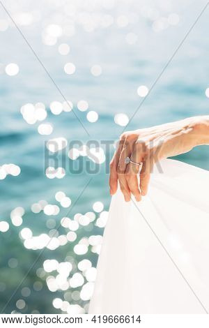 Brides Hand With A Wedding Ring On Her Finger, Close-up. The Bride Holds The Edge Of The Dress Again
