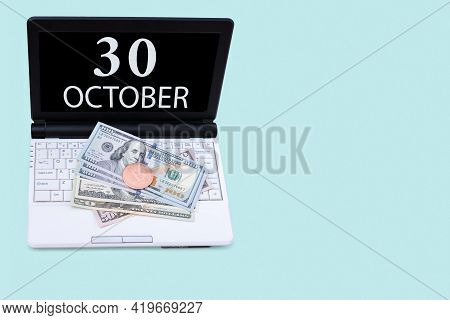 30th Day Of October. Laptop With The Date Of 30 October And Cryptocurrency Bitcoin, Dollars On A Blu