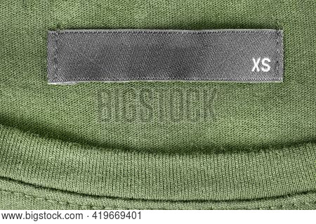Size Xs Clothing Label On Green Knit Background