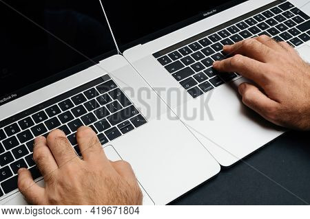 London, United Kingdom - Jan 9, 2018: Male Hand Operating Two Laptop Simultaneously Professional App