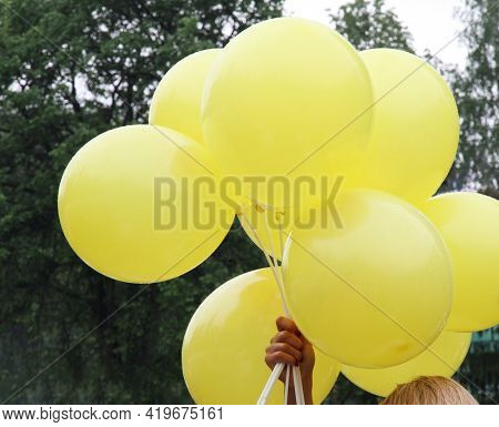 Yellow Balloons On A Stick In A Woman's Hand Over Her Head. Festive Fountain Of Balloons. Celebratin