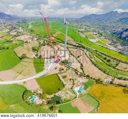 Wind Turbine Being Repaired, Assisted By Crane And Elevator. Wind Power Plant. Green Meadow With Win