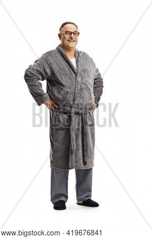 Full length portrait of a mature man in pajamas and a robe isolated on white background