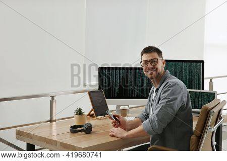 Happy Programmer With Smartphone Working At Desk In Office