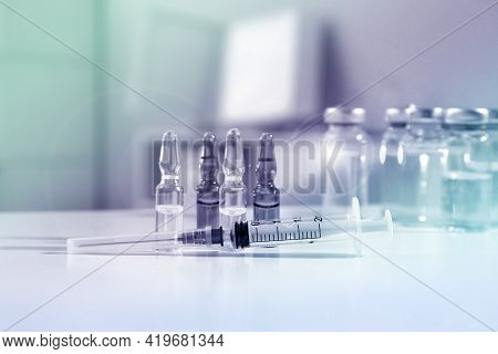 Syringe With Ampules Of Medicines On White Table