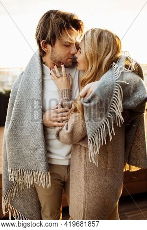 Portrait Of Beautiful Couple At The Sunset, Hugging In Cozy Blanket. Charming Loving Woman Gently To