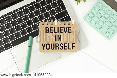 Notebook With Text - Believe In Yourself, On The Office Table, Documents, Calculator, Glasses And Pe