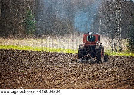 A Tractor Plows A Field. Preparation Of Agricultural Land For Planting. A Mechanical Plow Makes Furr