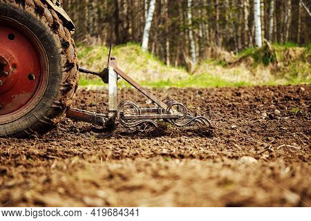 Plow Tractor Plows The Land For Planting Agricultural Plants. The Farmer Cultivates The Land In The
