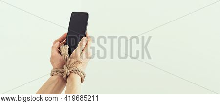 Hands Tied With Rope On A White Background, Suggesting Internet Addiction Or Social Media Addiction