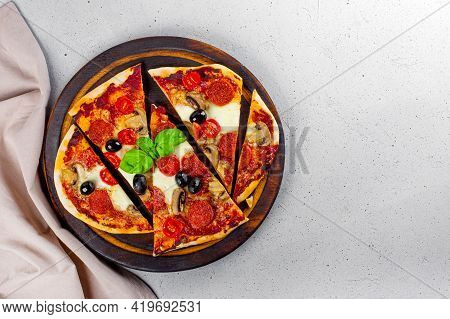 Fresh Homemade Italian Pizza With Mozzarella, Pepperoni Sausages, Olives And Basil On The Cutting Bo